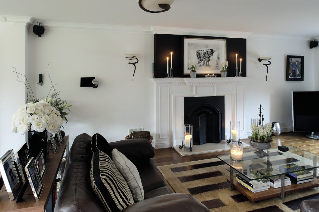 In the drawing room two mocha leather sofas surround the fireplace and a console table supports a collection of family photographs