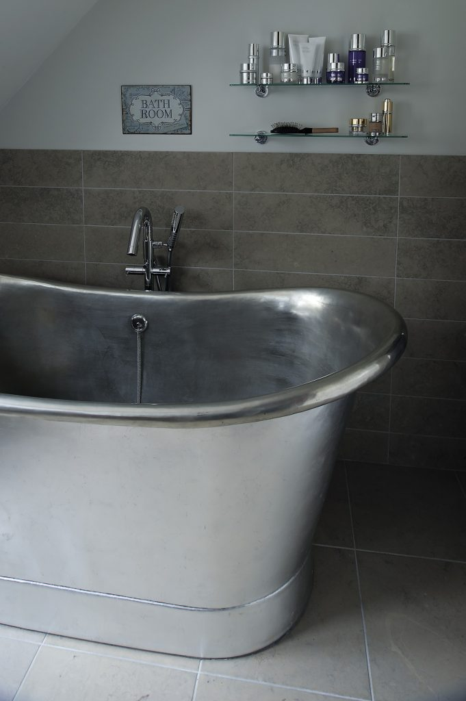 An enormous freestanding zinc bateau bath is the focal point of the master bathroom