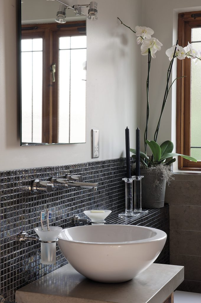The room has been tiled both with large rectangular Fired Earth stone panels and tiny glass mosaics