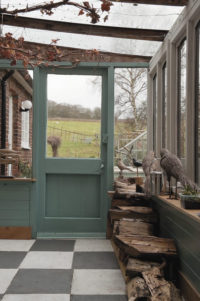 the concrete slabs in the lean-to conservatory have been painted to mimic a chequer board marble effect
