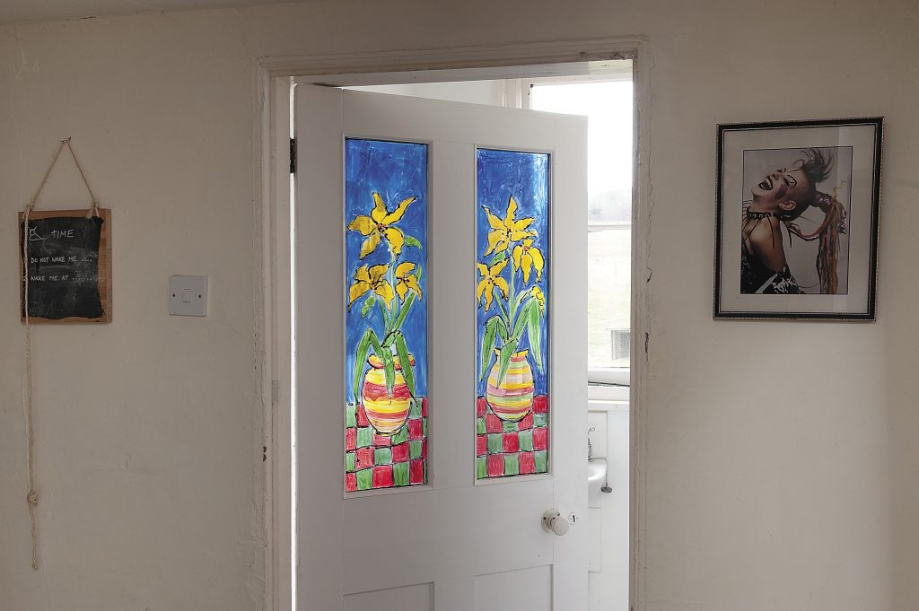 Sandy painted the glass in this bathroom door to create a stained glass effect