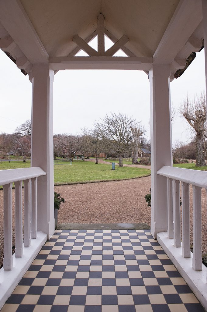 the Victorian porch on the front of the house looks out over farmland