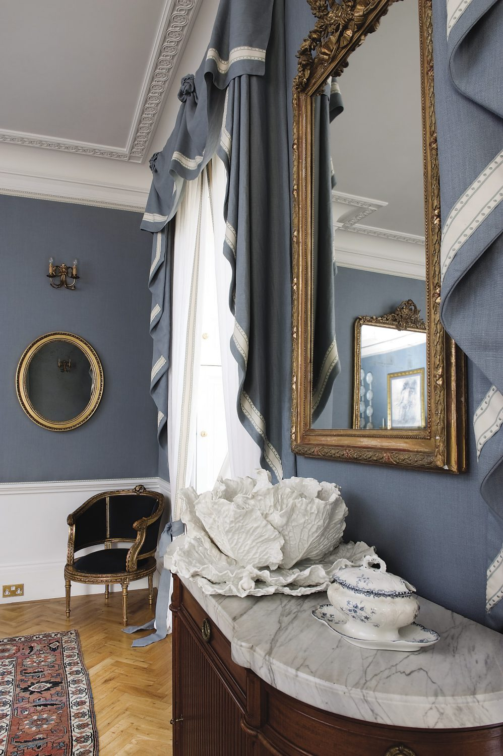 grey-blue linen from Libeco in Belgium covers the walls. The tureen in the shape of a giant cabbage with a snail on one leaf is from Astier de Villatte