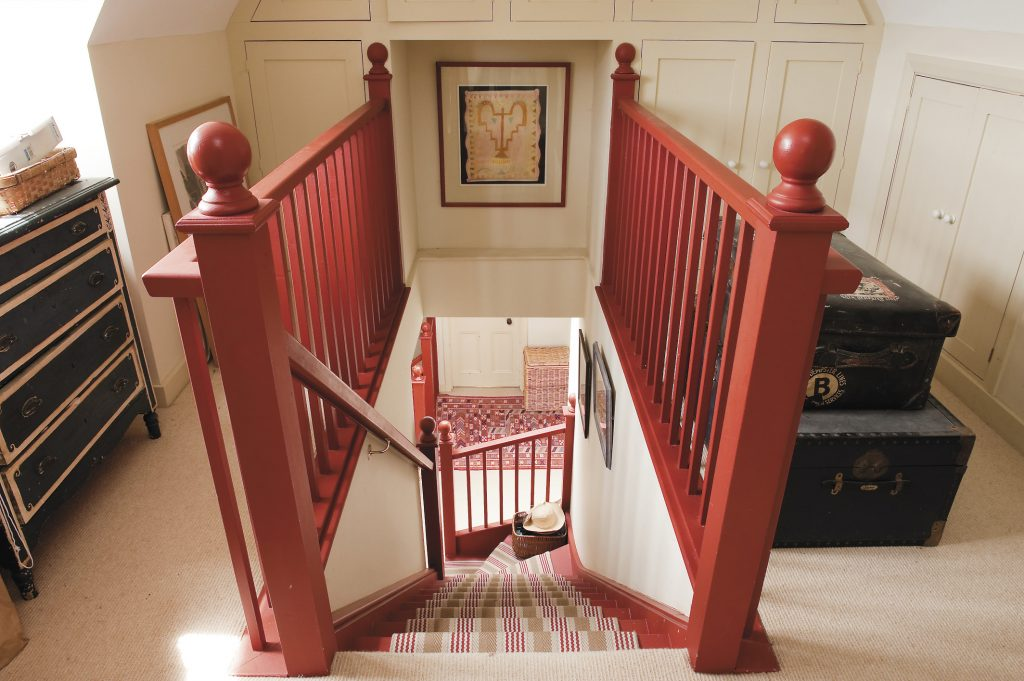 rust red banisters work very well against the oatmeal tones and tie together all the passages and landings in this higgledy-piggledy house