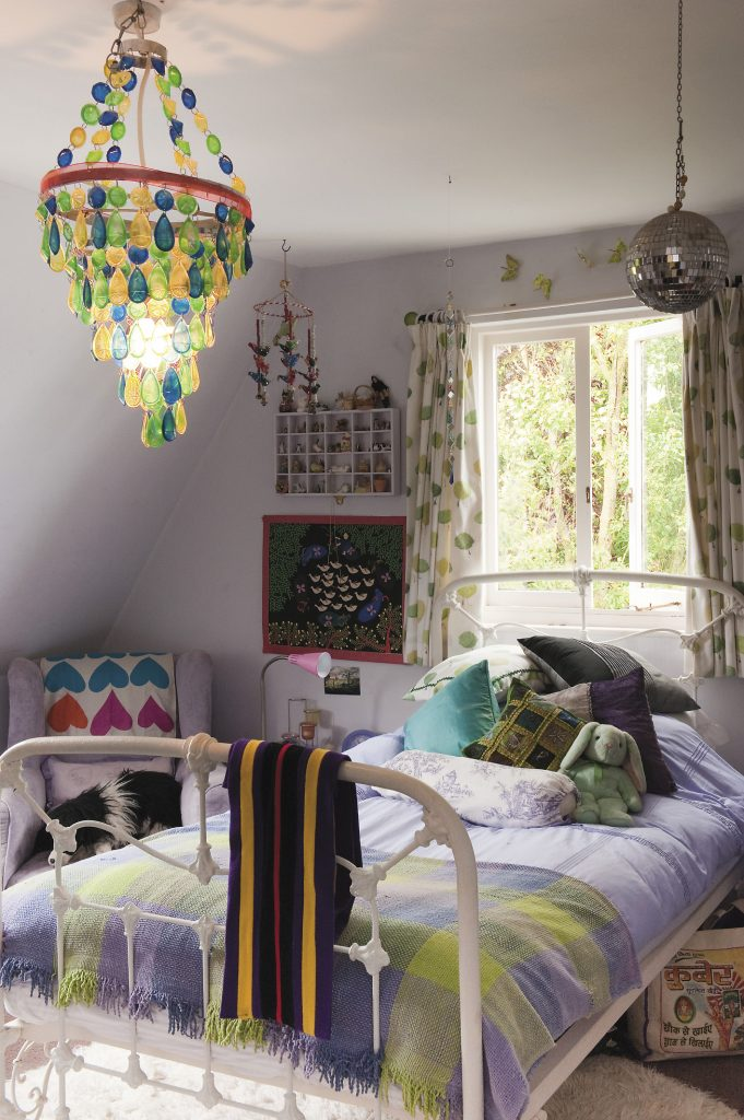 the blue and green glass chandelier adds a flash of brilliance in contrast to the lavenders and limes which work really well together to create a cool and restful bedroom