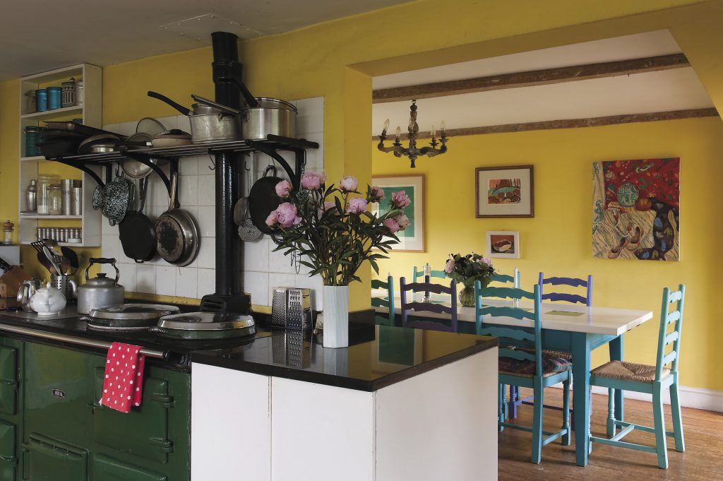 the kitchen, once a collection of smaller rooms and now dominated by a bottle green Aga, has been opened up to create a light and airy dining area. Victoria designed the dining table and then spray painted the chairs in a selection of peacock blues, emerald greens and turquoise