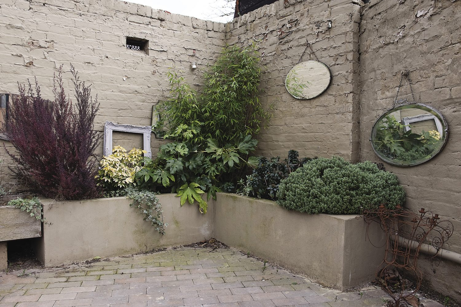 A corner of the paved courtyard,, decorated with mirrors and frames