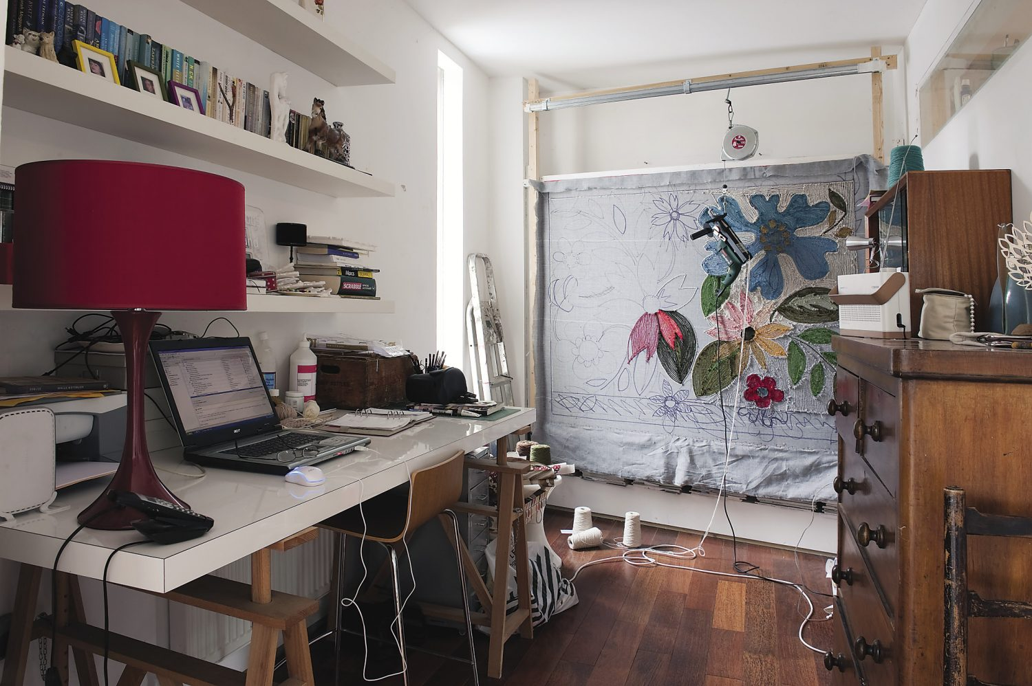 """Anna's studio is conveniently located in one corner of the airy bedroom; she is currently in the process of creating a vibrant floral rug. The design is based on the classic 1960s ceramics called """"Elizabethan"""" by Portobello"""