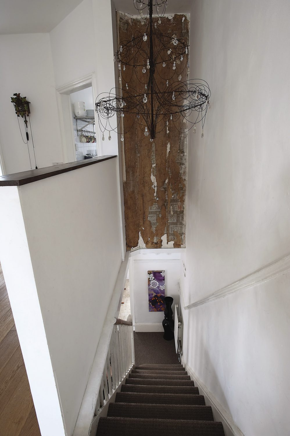 An intricate wire and glass chandelier, made by John, hangs above the staircase on the first floor