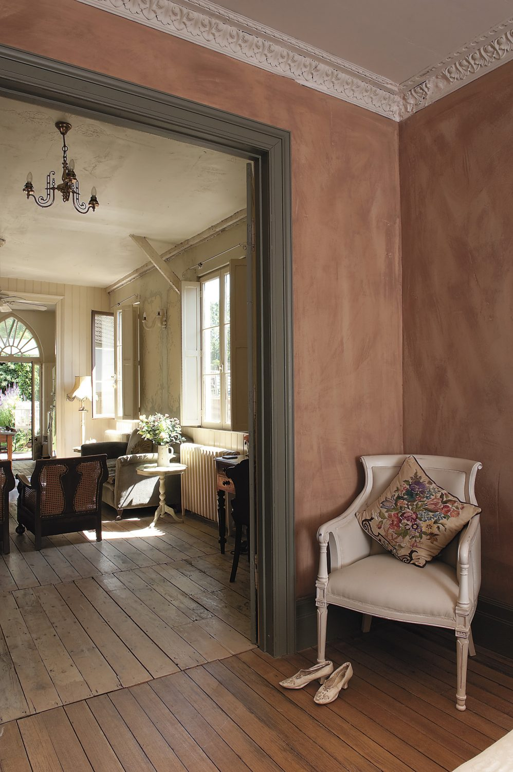 the airy master bedroom leads straight into the living room through an impressive set of antique French painted doors