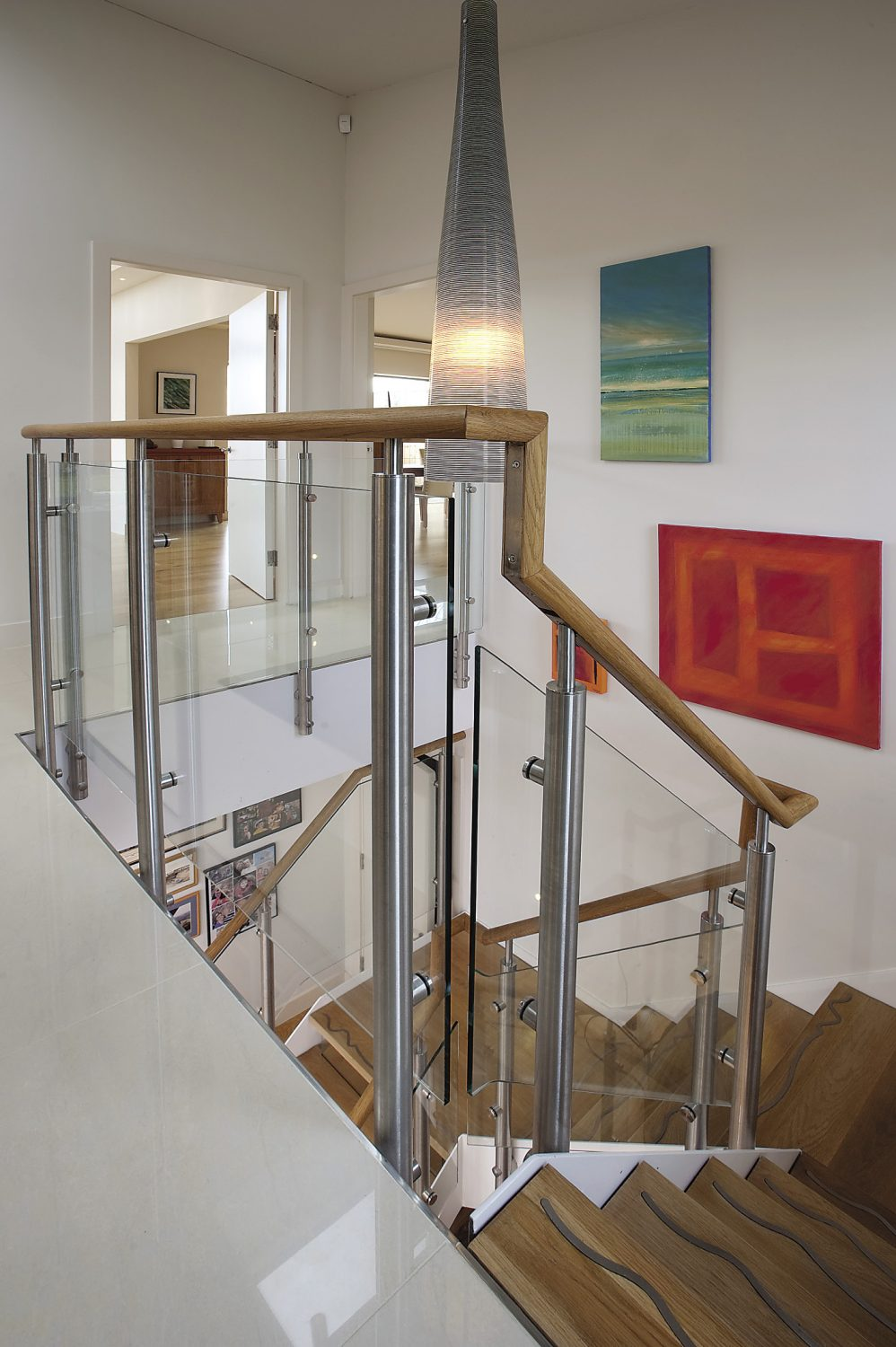 The steel and glass staircase leads down to a large open space that sometimes serves as a table tennis court