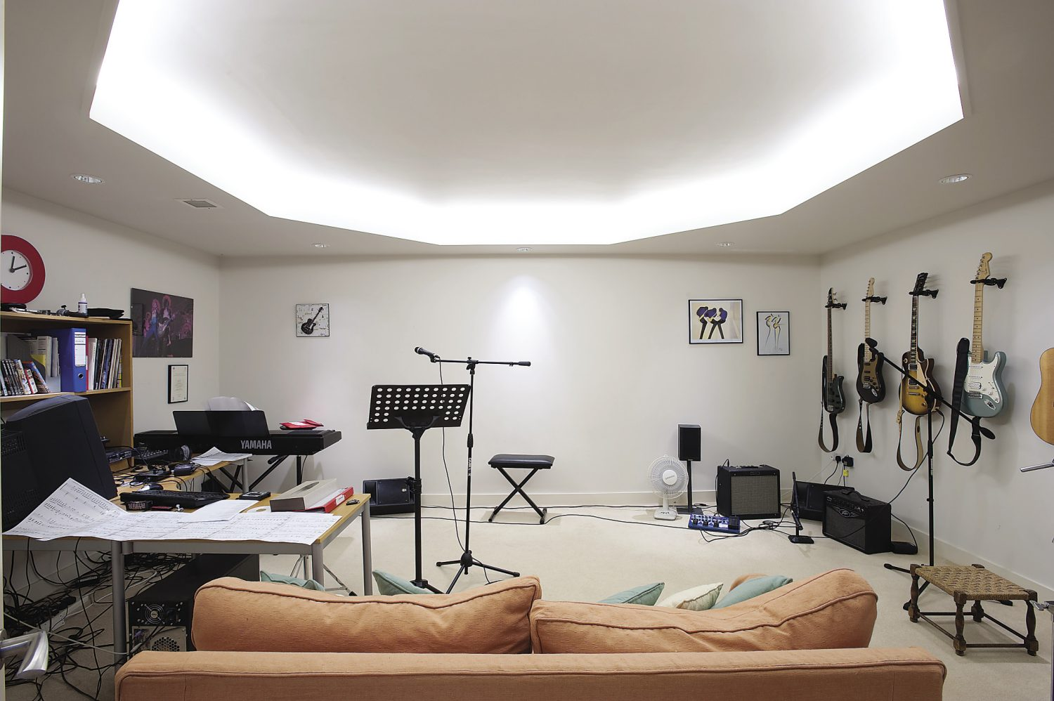 The music room is used as a home cinema, but its main function is as a rehearsal and recording studio for Tim to play guitar and for the couple's ten year old son to practise his jazz piano