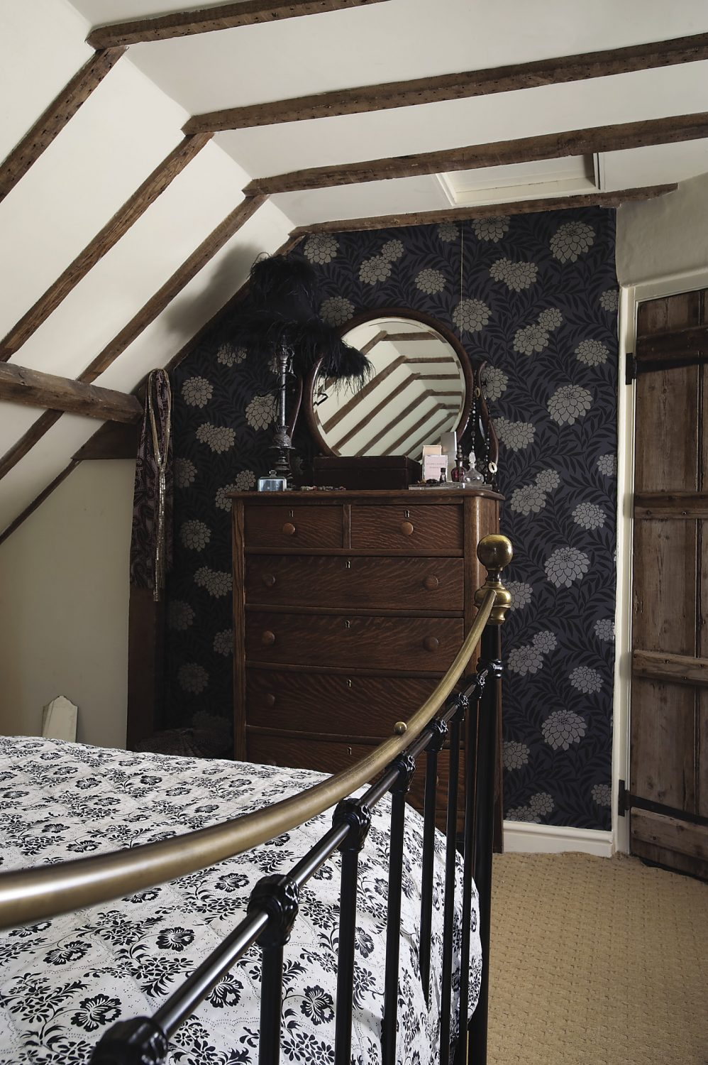 A bow-fronted white oak chest of drawers and mirror was a present from Stella's mother-in-law when she downsized, and a flamboyantly feathered lamp that stands on it, was from her own mother