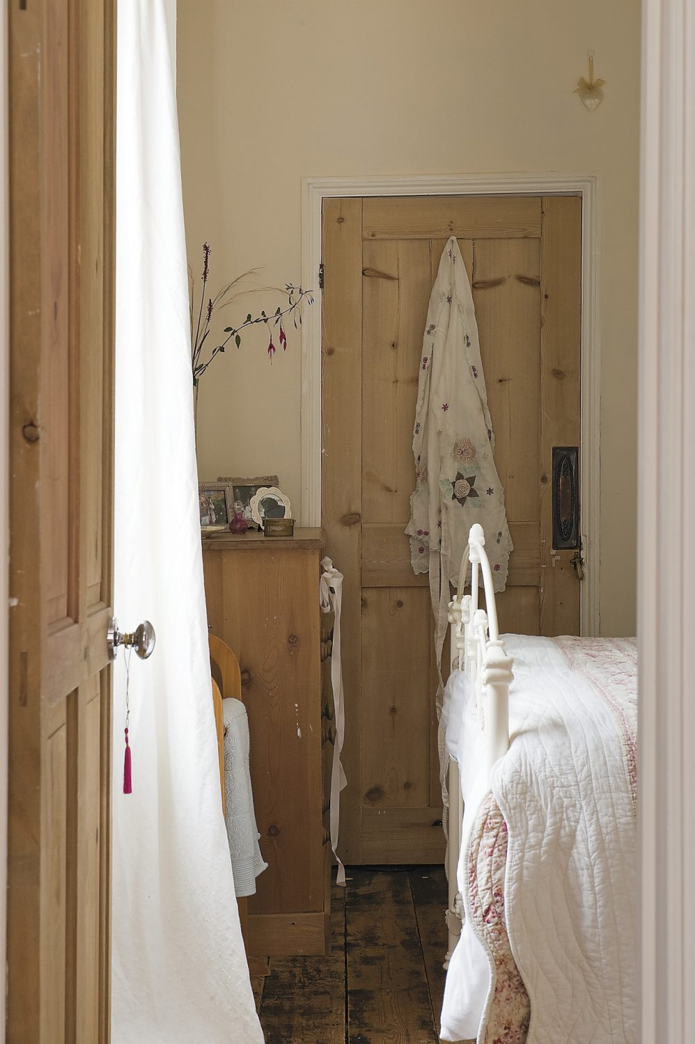 stripped pine and floral quilts in the spare bedroom continue the pretty country theme