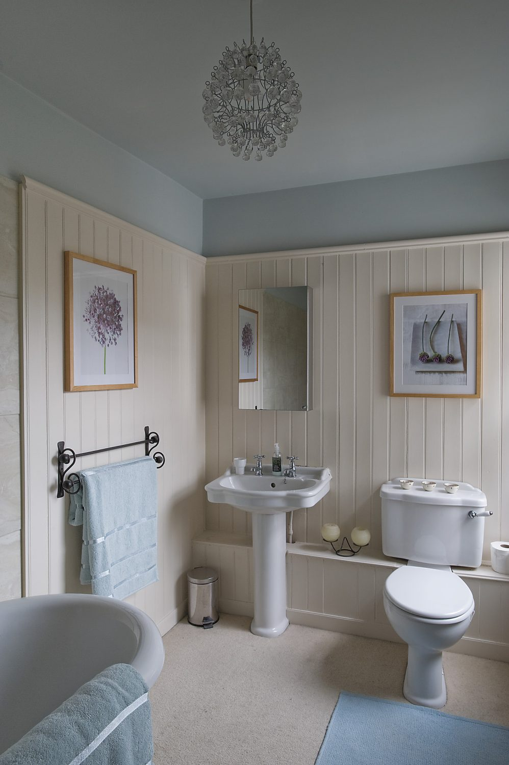 cream panelling and a roll-top bath in the bathroom