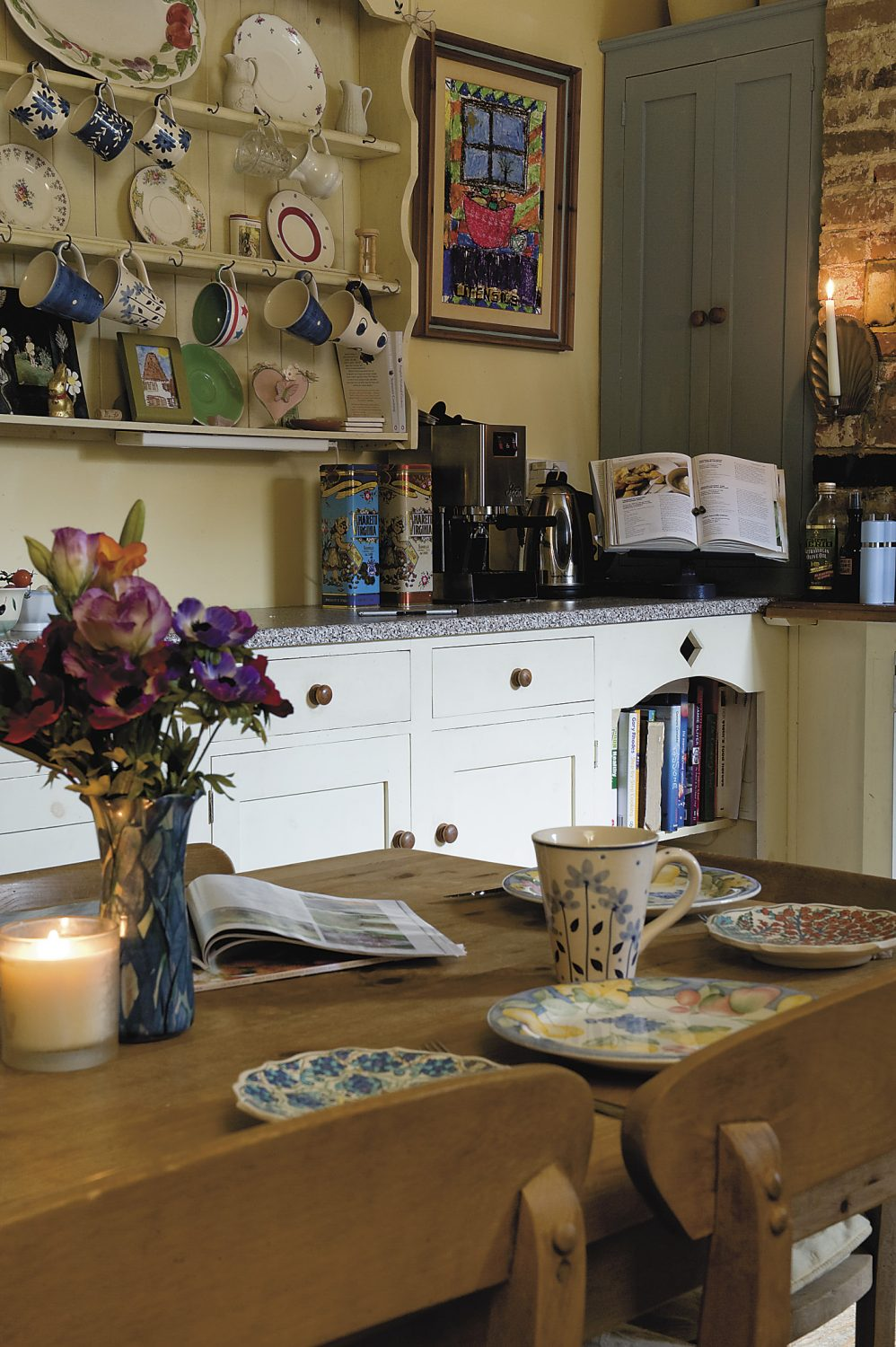 the handmade cupboards and exposed brick chimney breast in the kitchen create a country feel