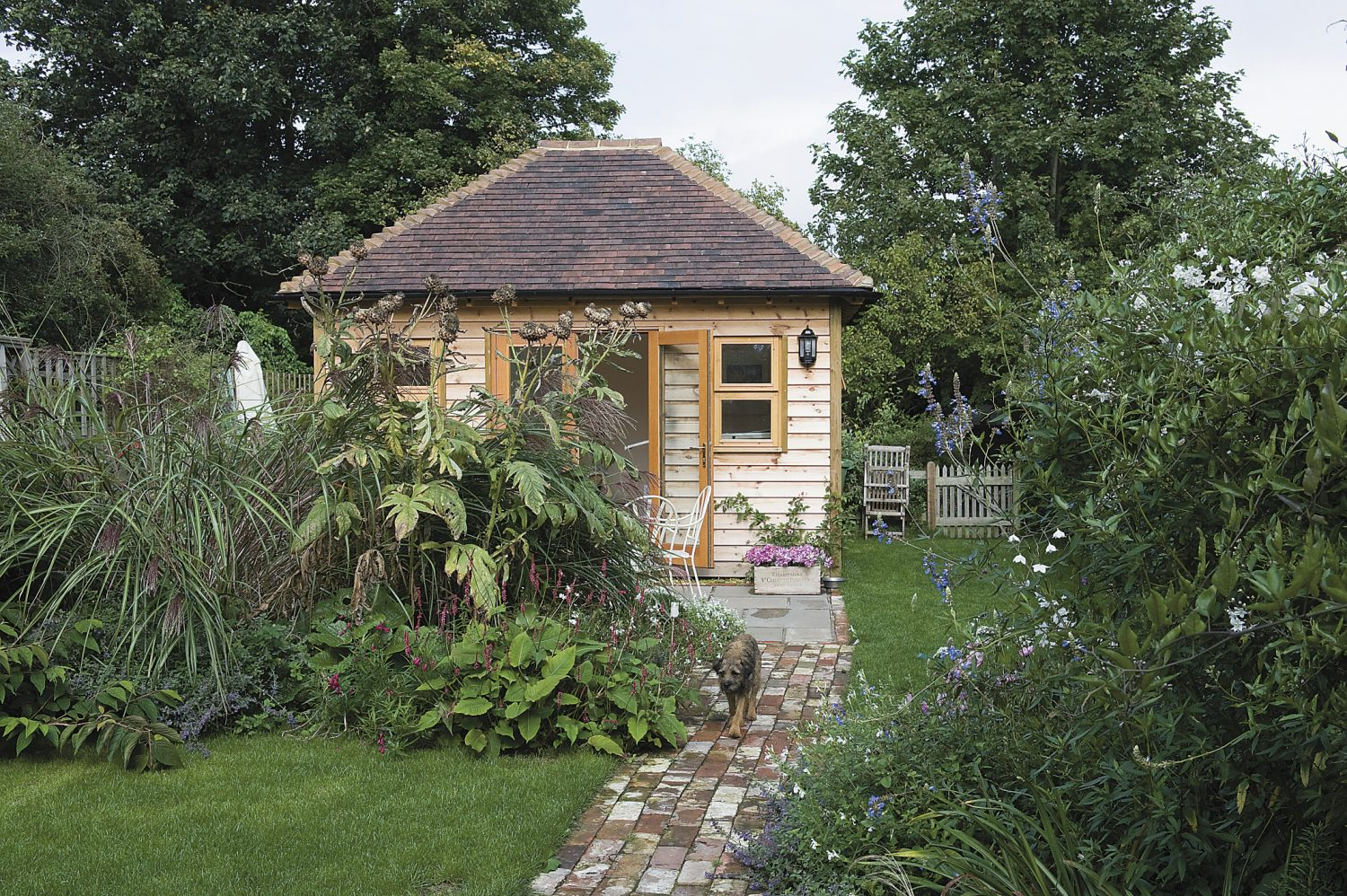 At the end of the garden is Kate's pride and joy: a garden office which she designed and had hand built. Inside, her drawing board has sketches and planting lists for gardens that she is currently working on...