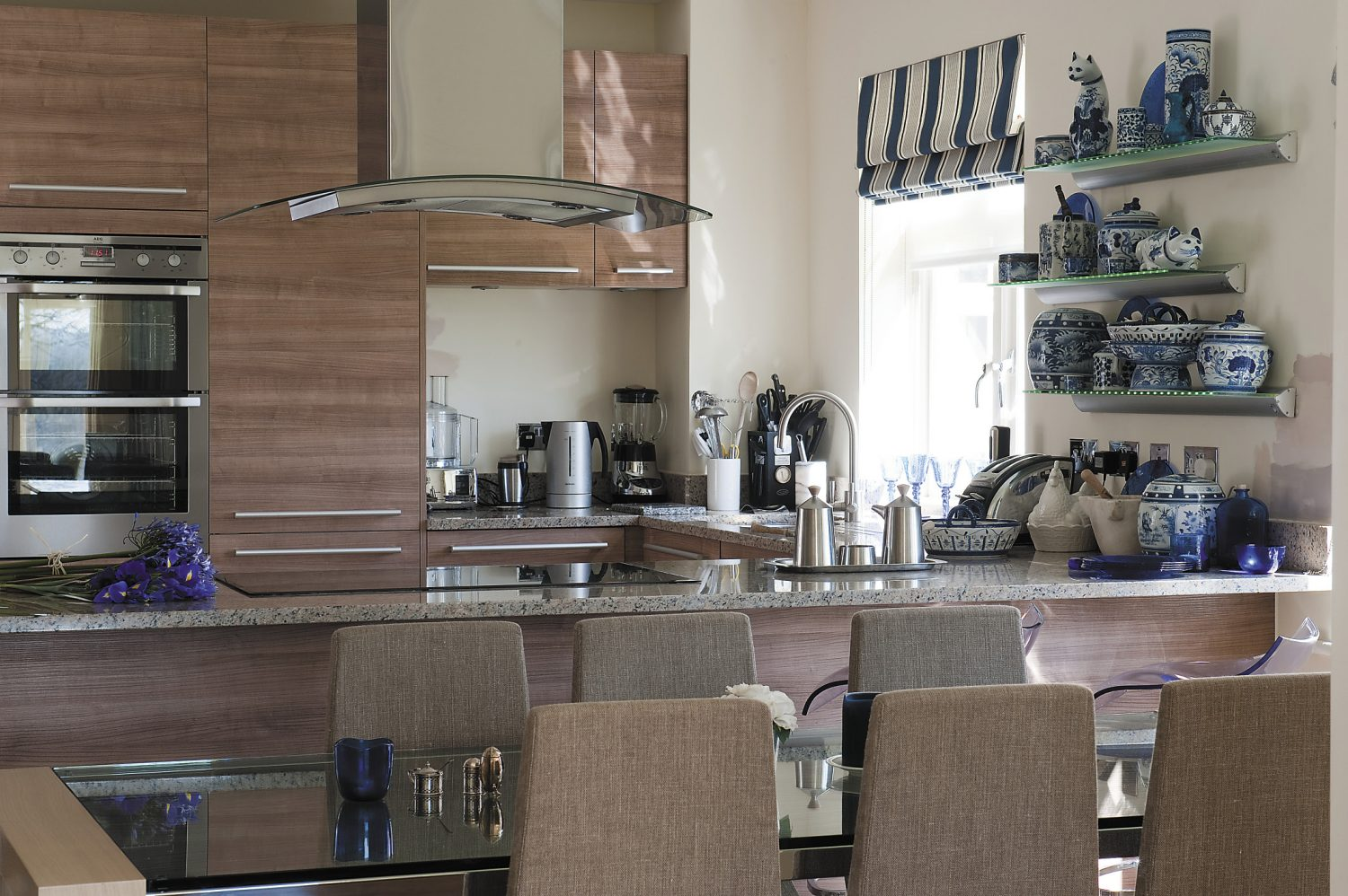 Jauntily striped cobalt blue and grey Roman blinds reinforce the colour scheme and complement the grey-beige tones of the sleek Italian kitchen units