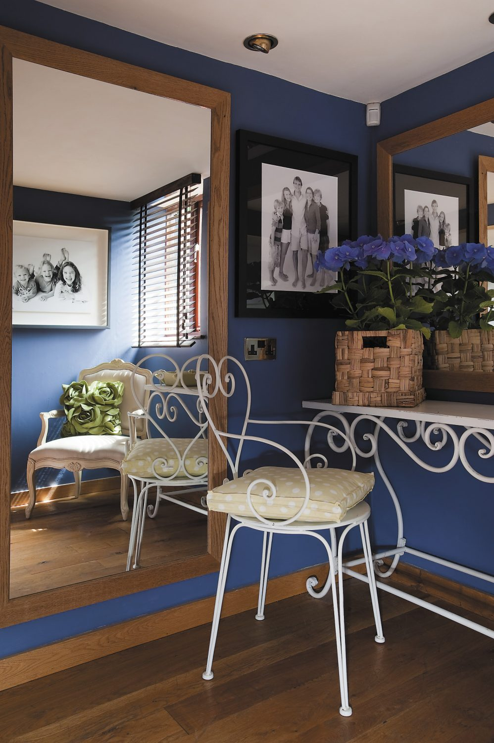 The walls of the dressing and sitting areas are painted rich reds and blues in contrast to the pure white of the workspace