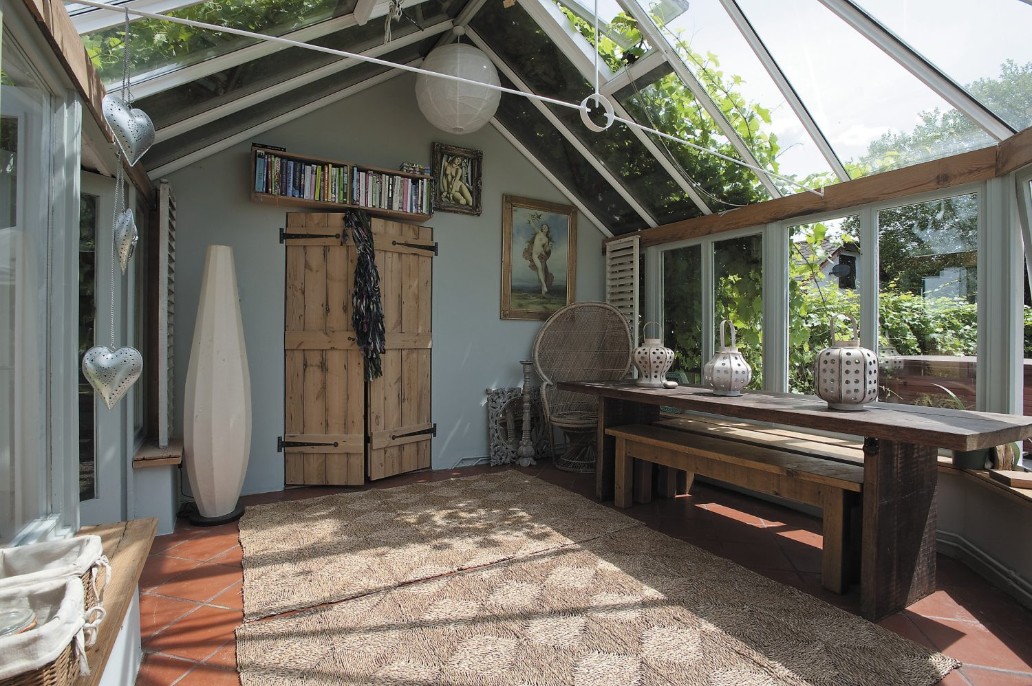 A huge grape-vine tumbles over virtually the whole house. It rambles, too, over the roof of the conservatory that, with its large rough mahogany table, makes a perfect dining room.