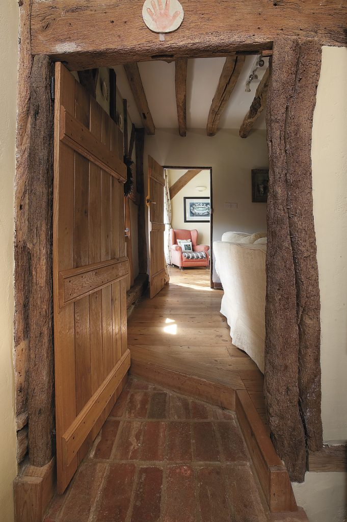 the view from the flagstone floored kitchen into the sitting and dining rooms; the oak doors have been carefully made to fit the curves of the centuries-aged walls