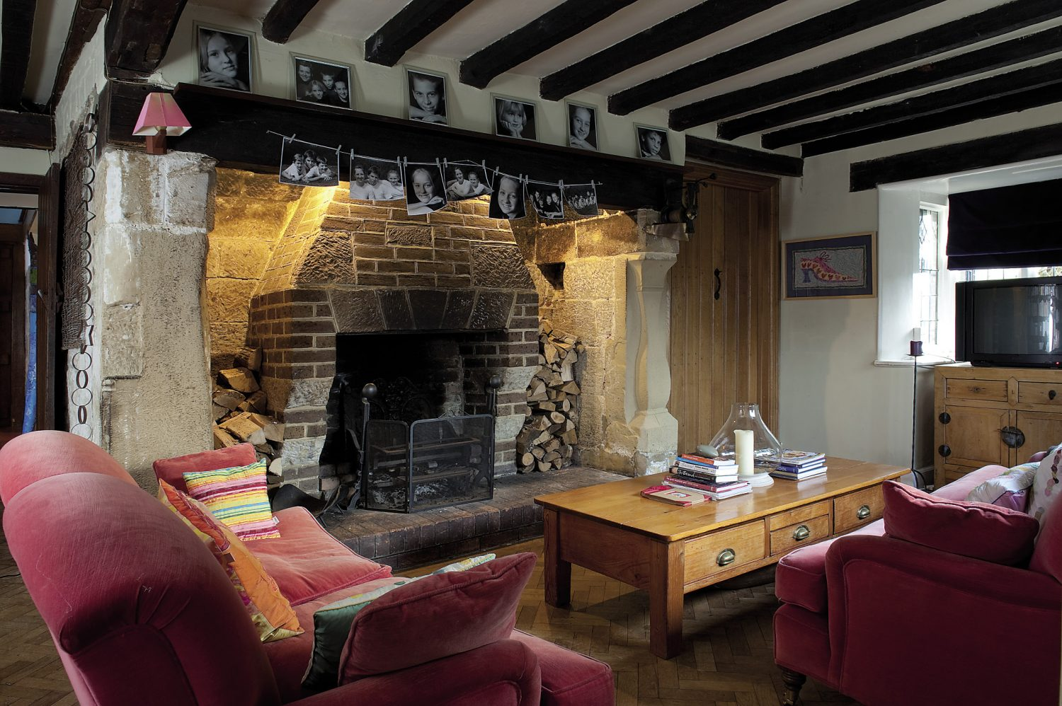 """One end of the library. A pair of sofas, upholstered in Zoffany pink velvet, nestle around the generously proportioned fireplace stacked with logs. """"We usually take these sofas out to the summerhouse in the warmer months,"""" says Gaynor"""