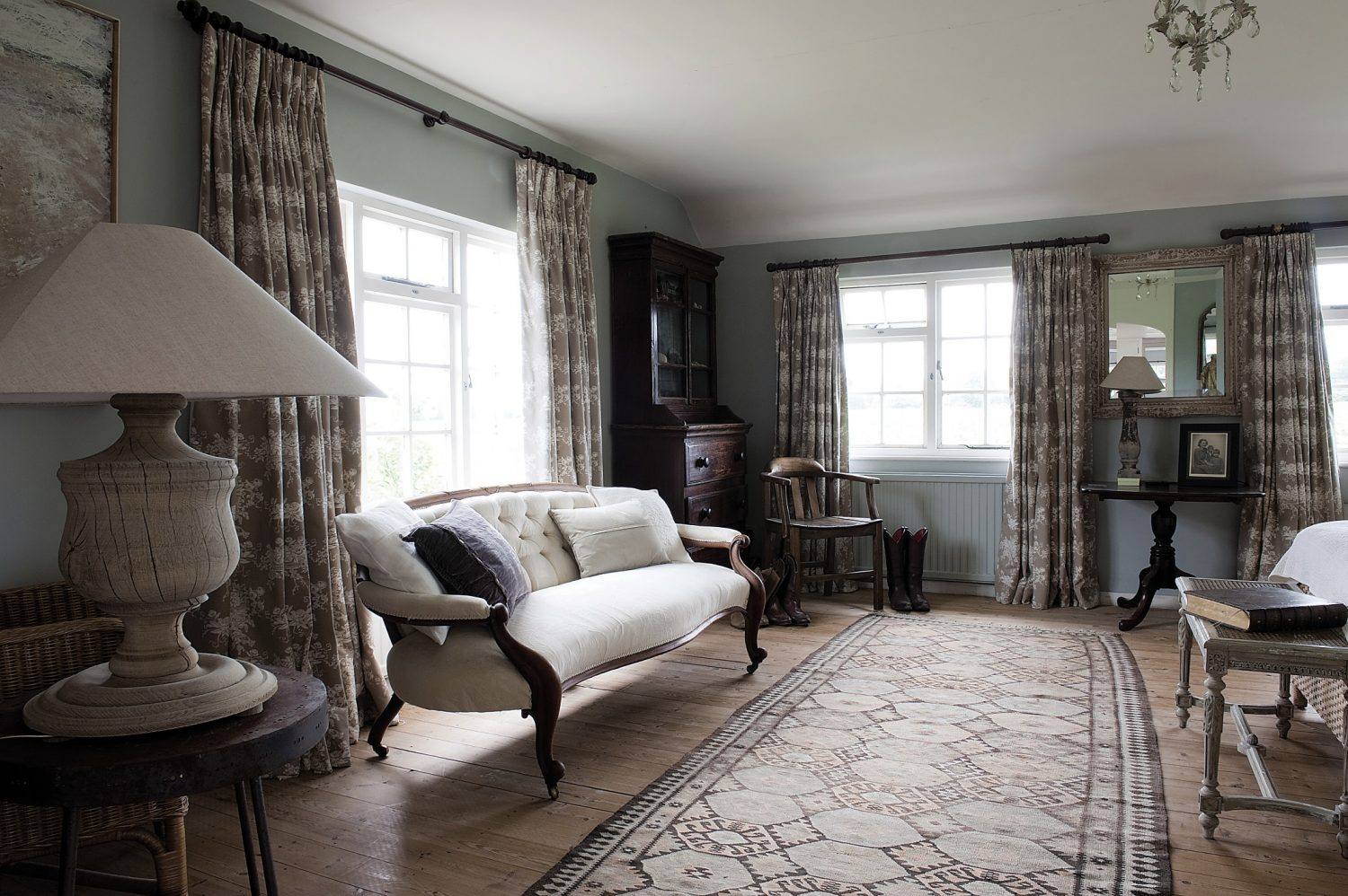The walls in the bedroom are painted in Farrow & Ball's Light Blue and the light brown and white unglazed curtains Veronica found in St Tropez. At the foot of the bed, by the window, stands an elegant white sofa