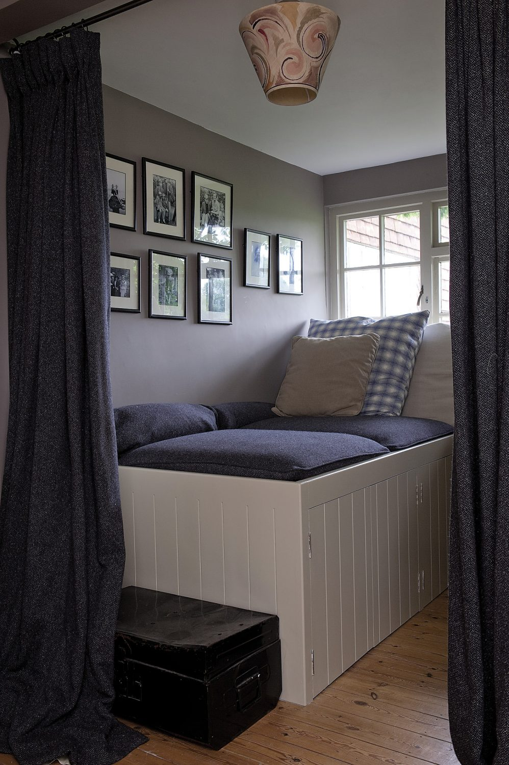 A tiny secret bedroom is hidden behind a curtain on the landing