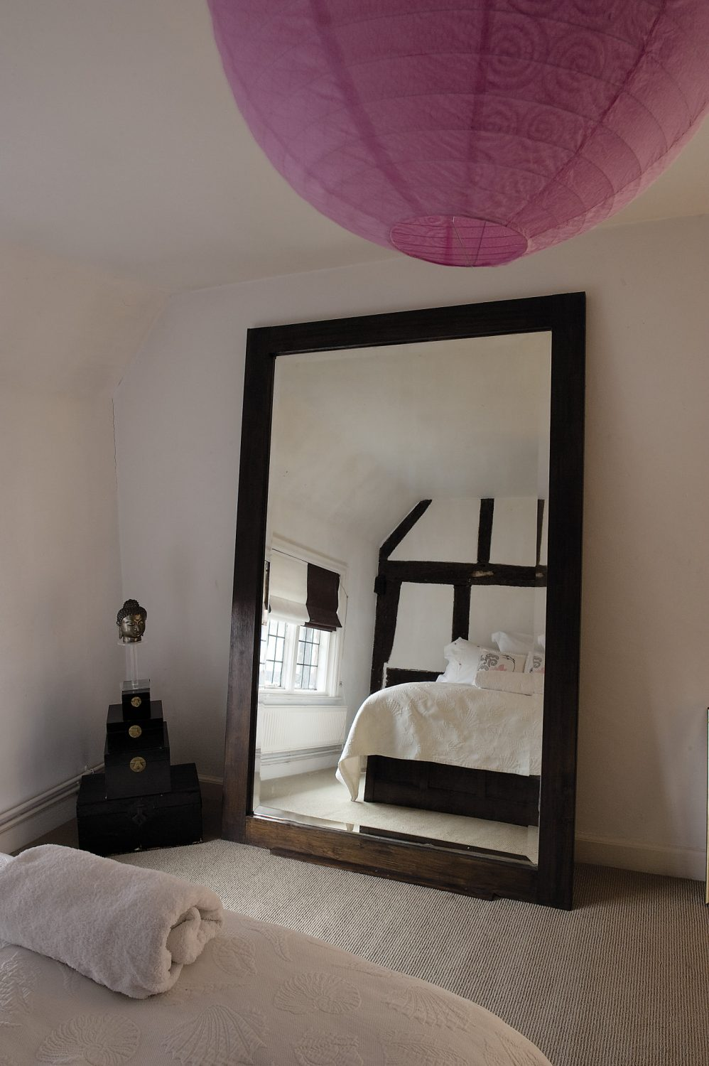 A guest room has been given the same chalky white walls as elsewhere but there is a chocolate brown and white striped blind, echoing the dark wall timbers, while the white bedlinen is dressed with pink embroidered cushions and a Japanese lantern made of textured pink paper hangs above