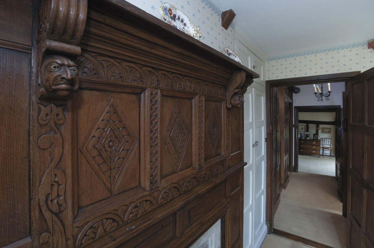 the central reception room is typically Tudor with its dark oak panelling, and linen-fold carving