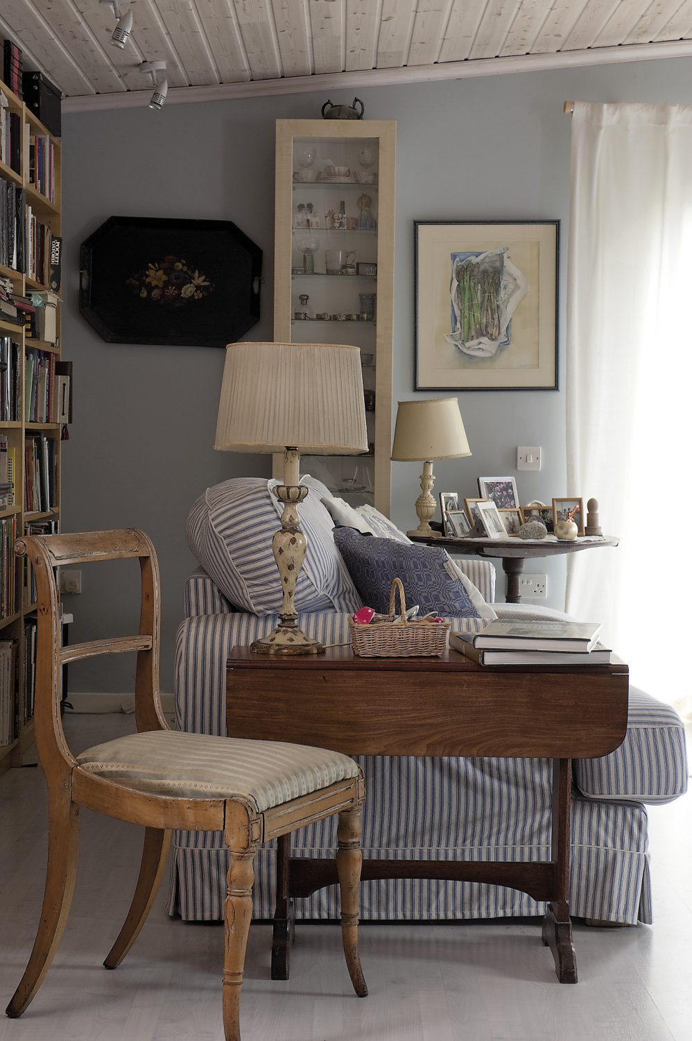 The sitting room is filled with large comfy sofas covered in blue and white ticking
