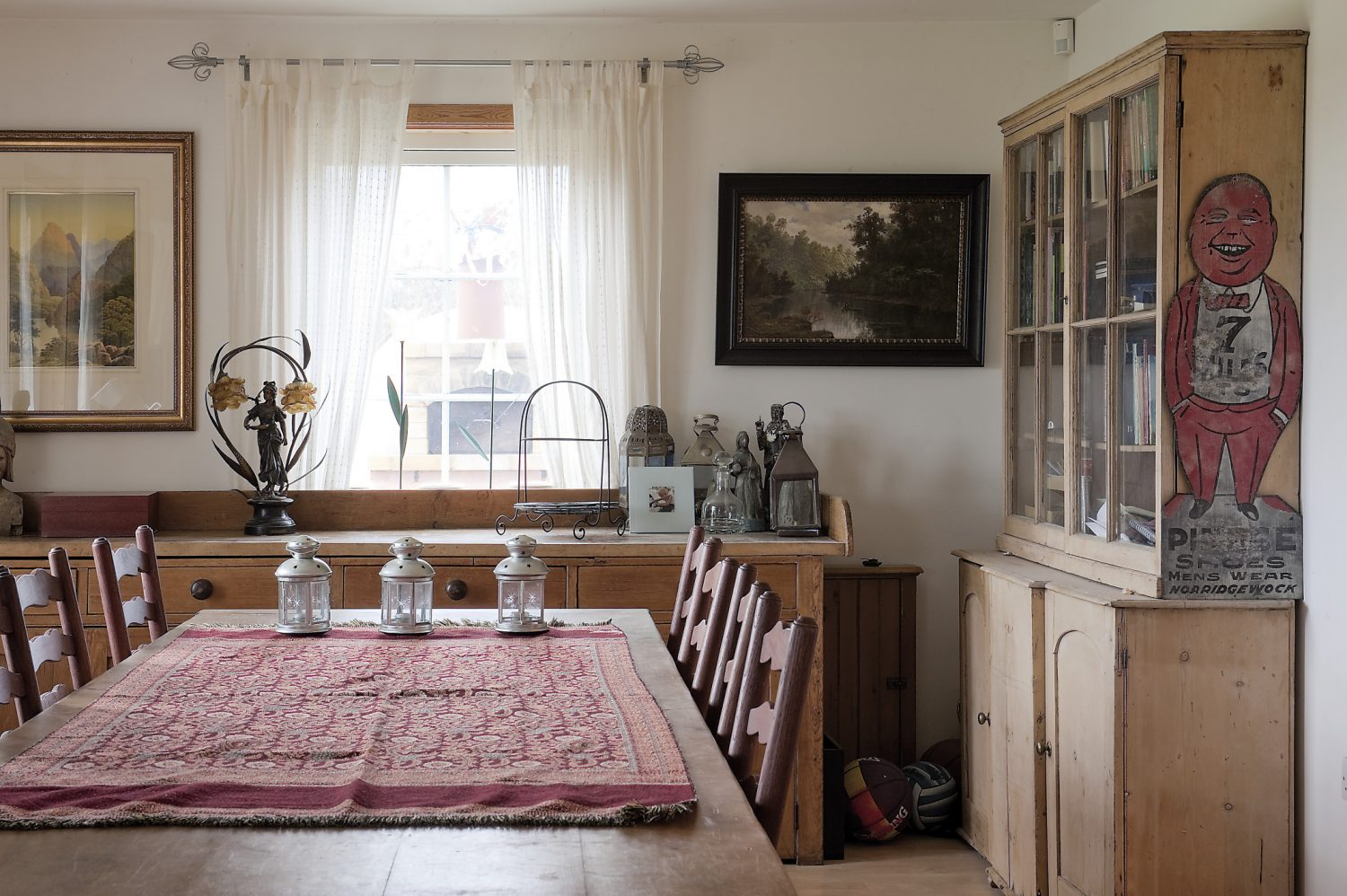A large table in the open-plan sitting and dining area was commissioned from a joiner at The Old Forge in Appledore, and is home to a few quirky collectables – such as a bacon slicer and a tin man advertising a downtown shoe shop somewhere in the American Midwest