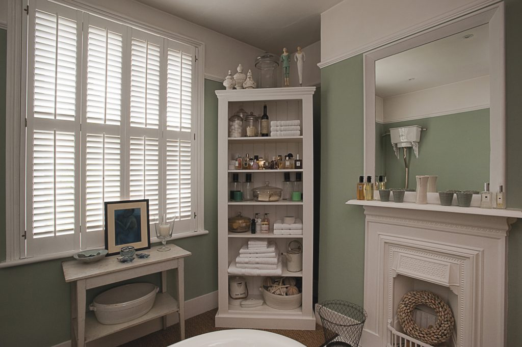in the bathroom the walls are a suitably oceanic blue-green and the furniture and shutters are white while the seagrass flooring adds texture. The roll-top bath has antique brass taps