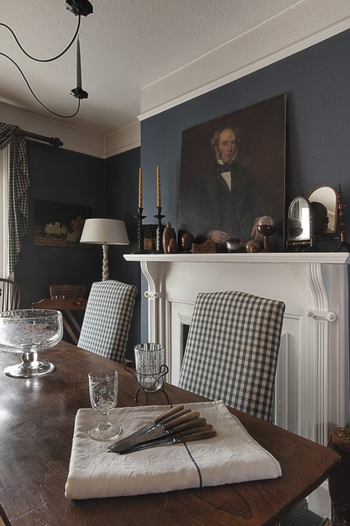the dramatic dining room is painted a deep teal blue and creates the perfect backdrop for dinner parties