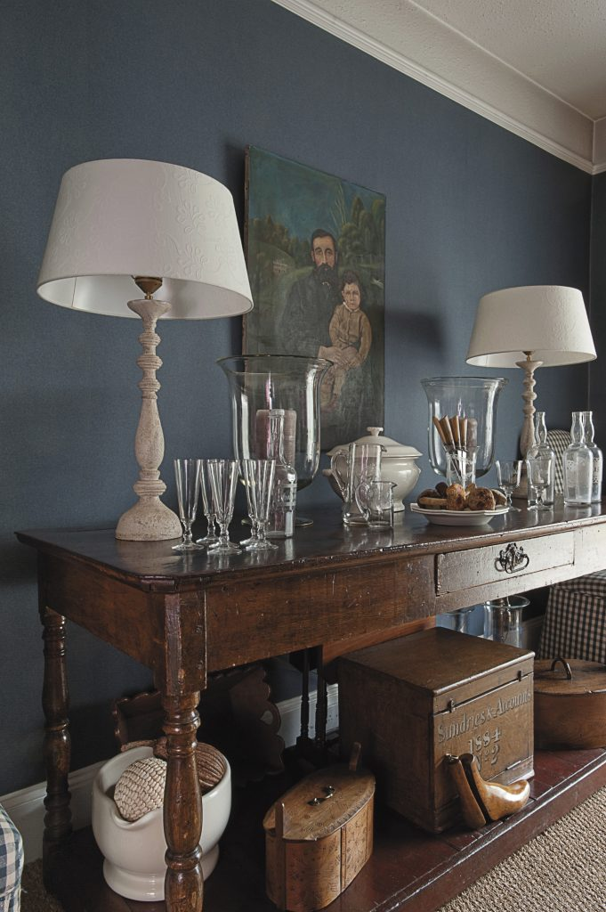 the French fruitwood table in the denim blue dining room displays a large cream soupière in the centre, a pair of linen-shaded lamps at either end and a collection of 18th century etched glasses and spirit bottles. The oil painting on the wall is in the naïf style