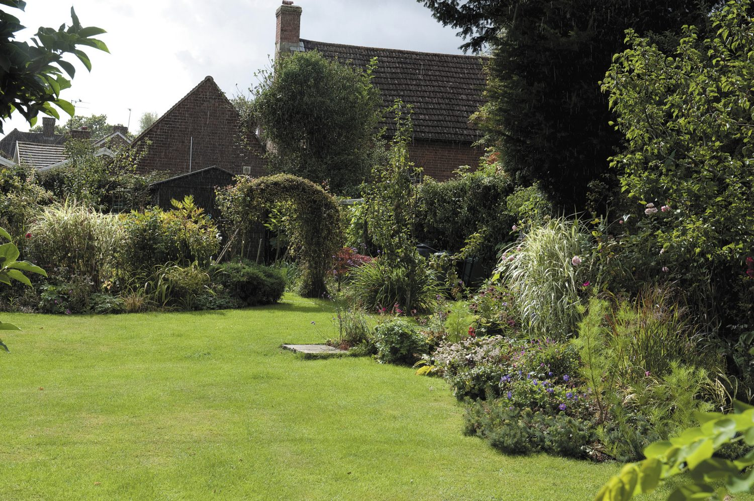 both Fanny and Vivian enjoy sharing the gardening which is a labour of love; the roof of the old schoolhouse can be seen at the end of the garden