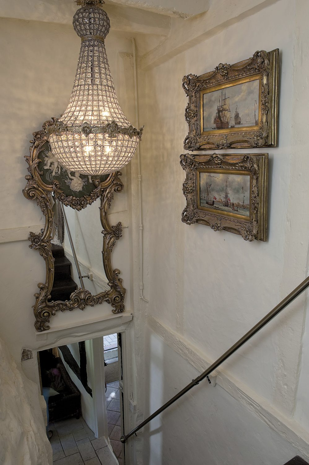 Opening a door to the side of the chimney-breast, Andrew reveals the stairs to the first floor. Above our heads an extravagantly gilded mirror and French Empire-style chandelier set the tone