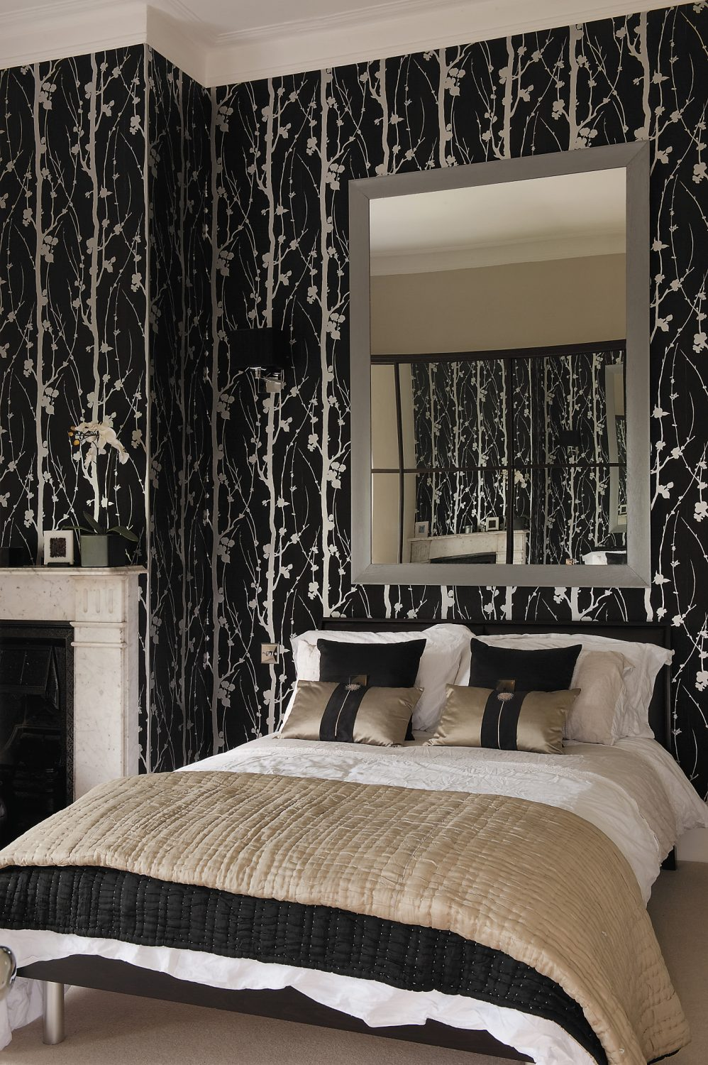 The first-floor guest room. At over three-and-a-half metres, it's the highest room in the house and its height is accentuated by the striking vertical pattern of the black and silver wallpaper