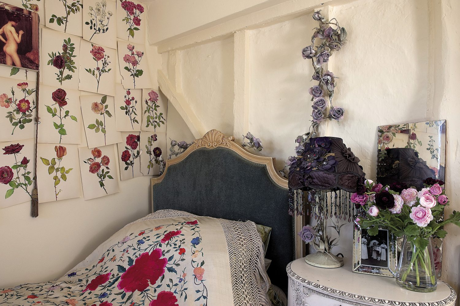 """The last, smallest bedroom is packed with more vintage finds. """"When I bought the house, this room was painted pink and the beams had been stained black, which I found really oppressive, so I changed it to white and then put all these rose prints from an old book on the wall,"""" says Andrew"""