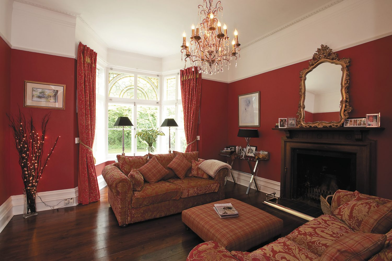 In stark colour-contrast to the rest of the house, the drawing room features deep red walls and chunky sofas