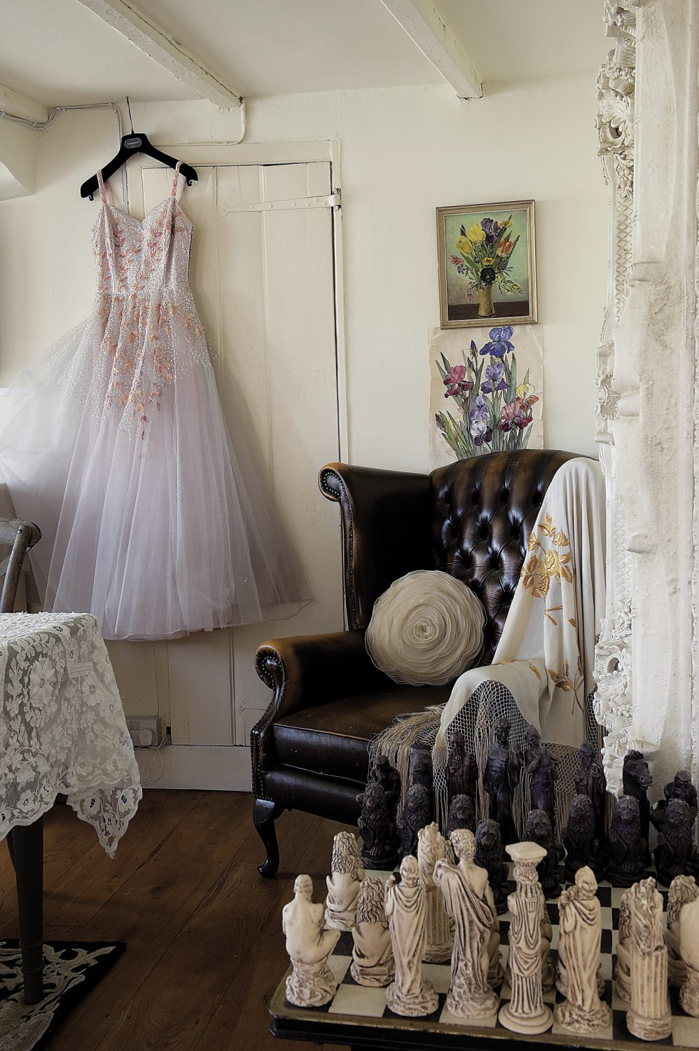 """The dining room. Hanging on one wall is a vintage 1950s gown made of pale, shell pink silk with layers of pearl grey tulle and a cascade of appliquéd blossom on the bodice. """"I love vintage style. I like the elegance of the dresses of the 40s and 50s and find them really inspiring,"""" says Andrew"""