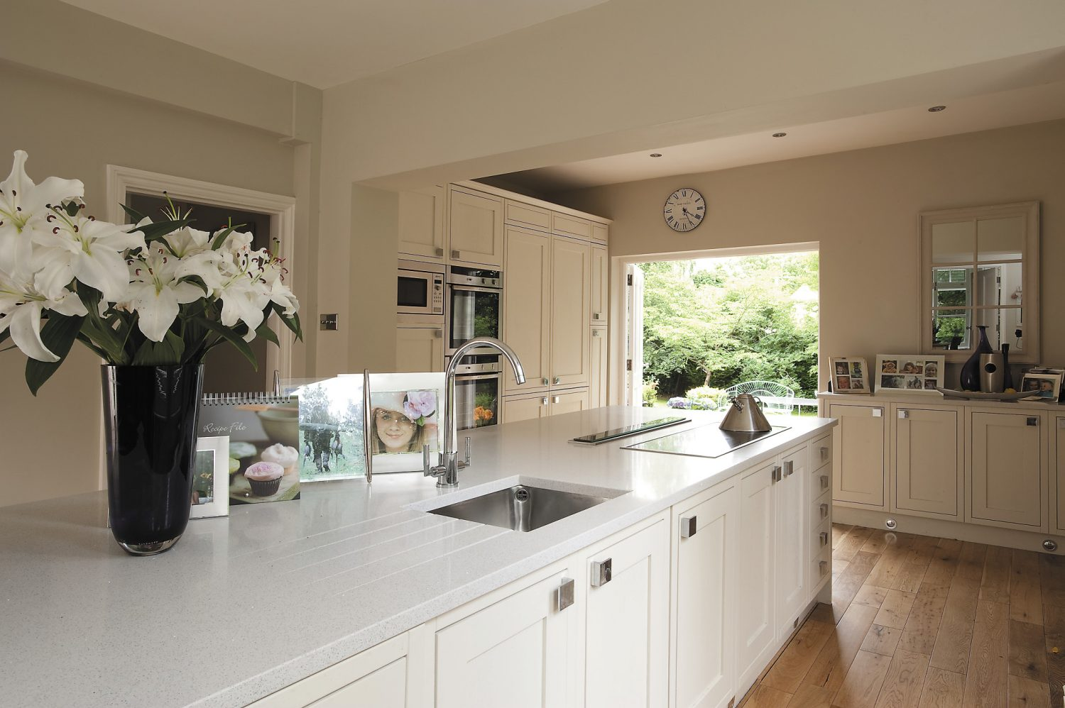 At one end of the kitchen large French doors lead out onto a terrace and down to the lawn