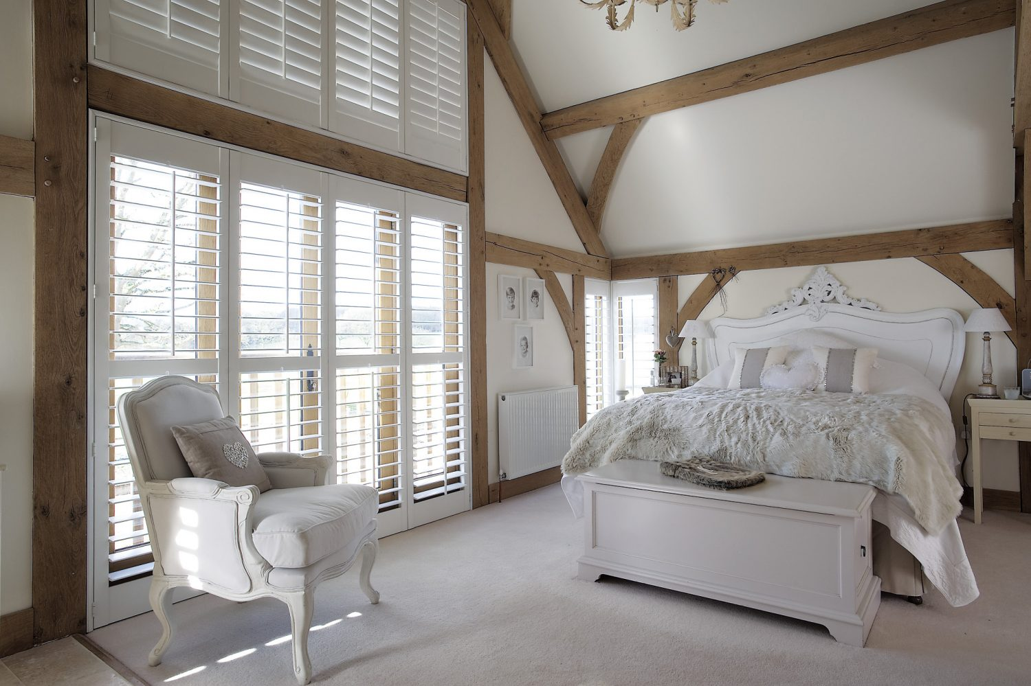 A careful use of symmetry in the master bedroom and bathroom creates a serene atmosphere. The carved and painted wooden bed was bought in Paris and is simply dressed with Portuguese piqué cotton. On a pair of bedside tables stand candle-style lamps with monogrammed linen shades bought from Charlotte Casadejus at the Wealden Times Christmas Fair. The simplicity of the scheme shows off the pale honey coloured oak beams to great effect