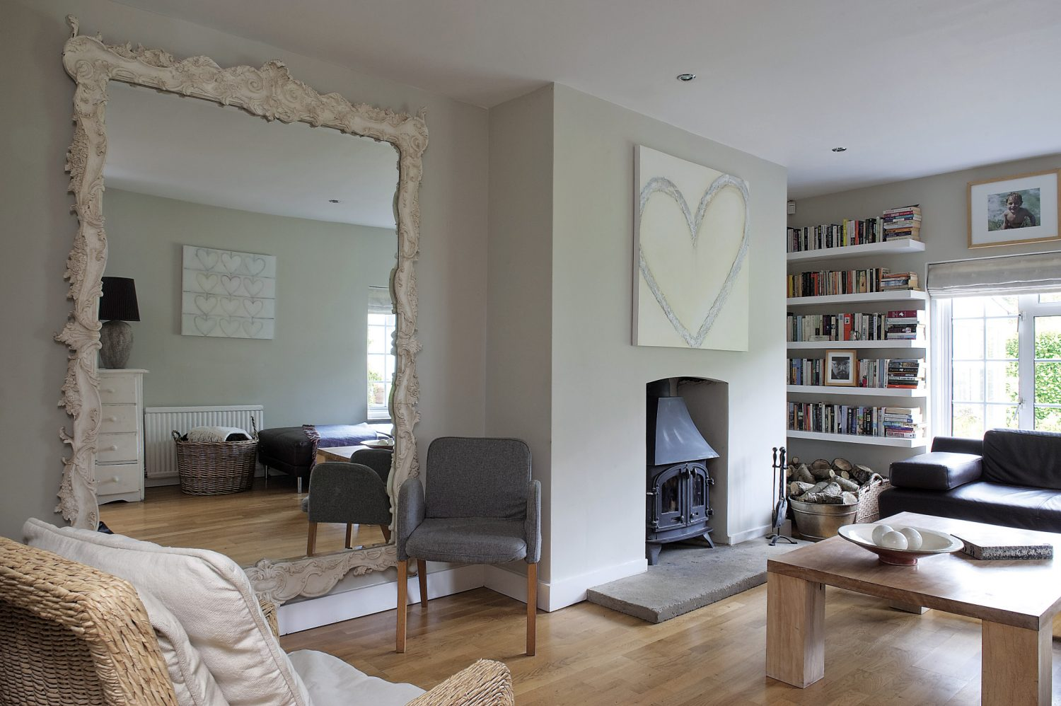 """Over the woodburner in the sitting room is another of Sara's large canvases, a single heart in encaustic. """"I love the medium because it's tricky to work with and you never quite know what you're going to get."""""""