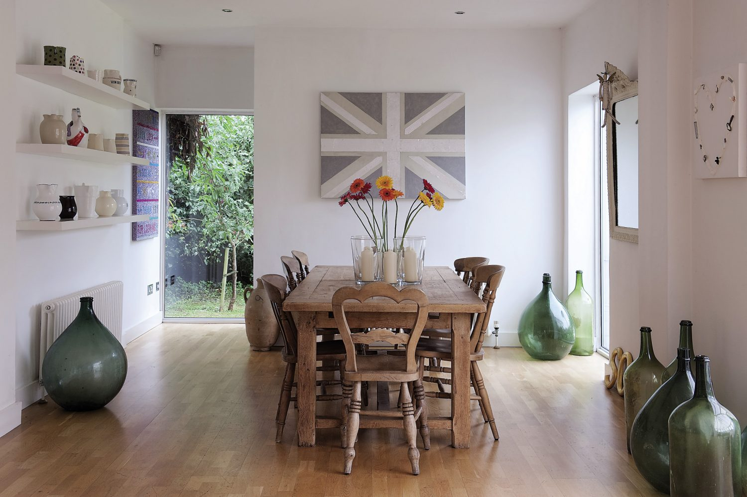 The light oak floor of the kitchen extends uniformly through the house and contributes, along with the white walls, to the overall feel of light and space. On the opposite wall to the kitchen, at the other end of the kitchen-dining space, is a fun, silver leaf Union Jack