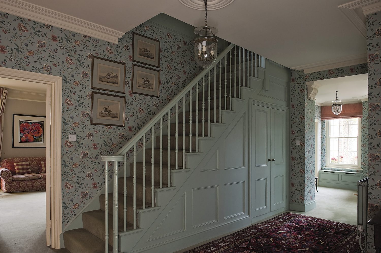 A broad staircase has its original Regency banisters. Sophie has painted them in Farrow & Ball's 'blue-green' to match the rest of the wooden panelling