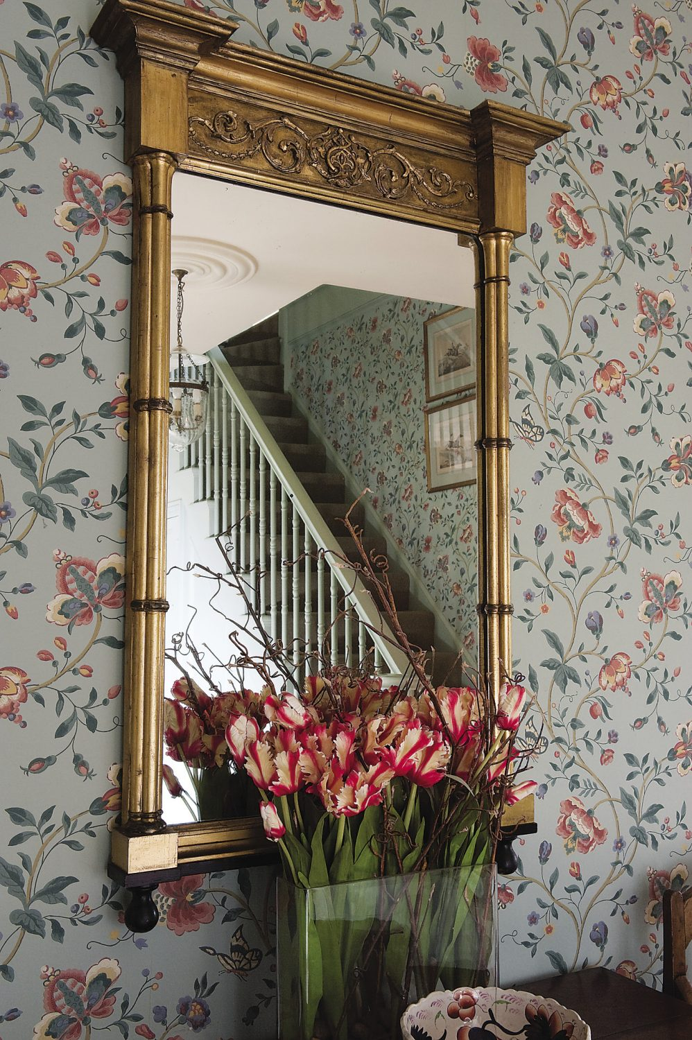 The walls of the hallway are smothered in the flowers and butterflies of an exuberant Nina Campbell wallpaper
