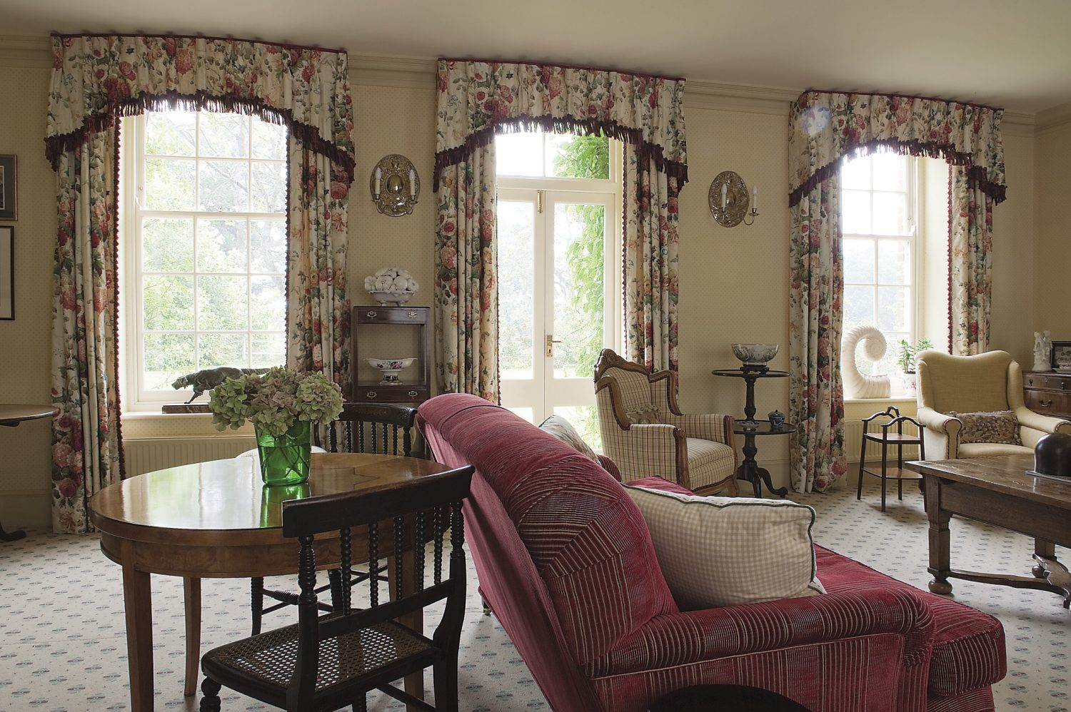 Sophie's use of pattern is bold and assured. The curtain fabric, generously draped in the drawing room, is by Colefax & Fowler