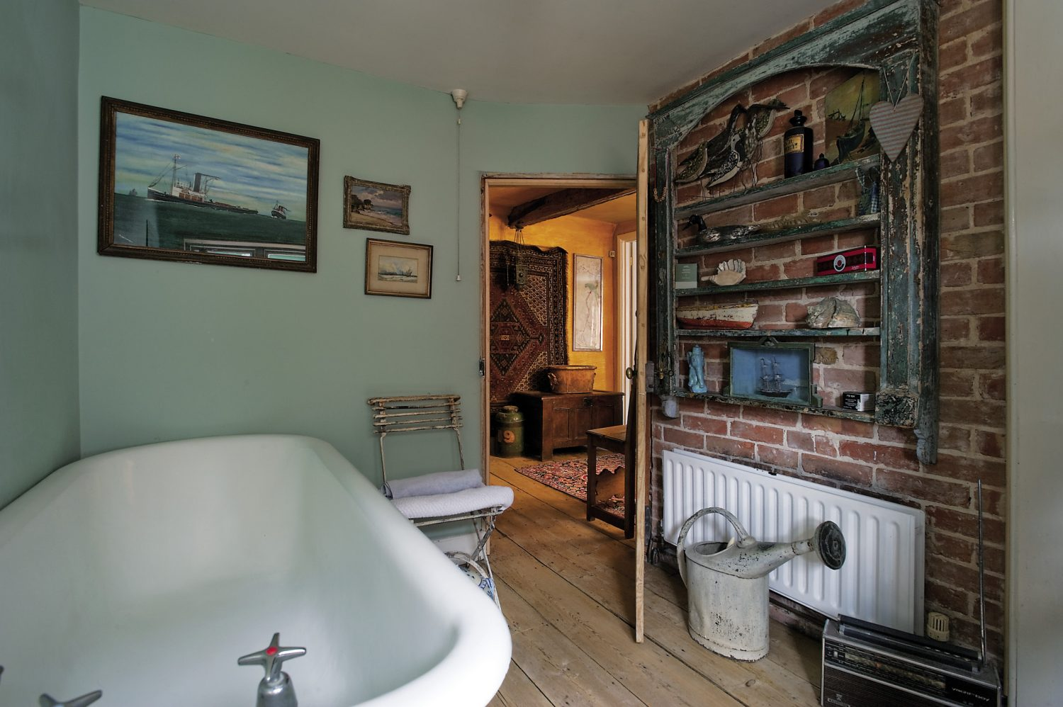 In the sea green painted bathroom a vintage rolltop bath seems fathoms deep and next to it stands a 19th century metal Arras chair, made in the town of the same name in northern France