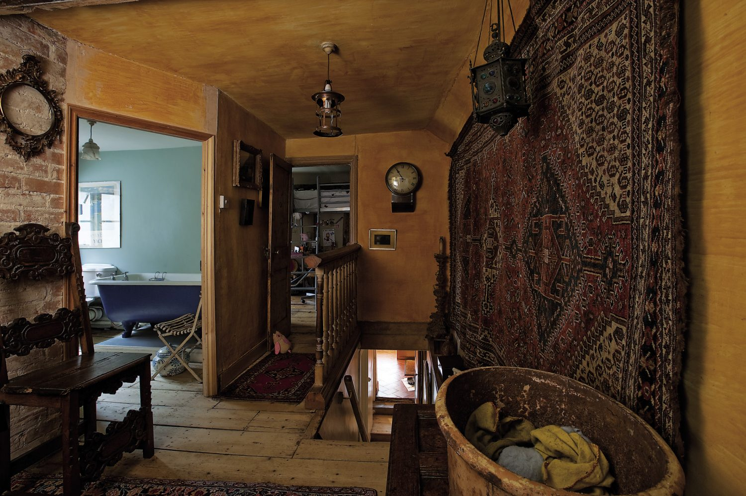 Up a narrow flight of bare pine steps is the landing, where the walls and ceiling have been painted with a rich ochre yellow wash. A rare, 19th century Qashquai rug hangs on the wall